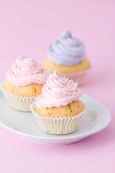 Cupcake met roze en violette buttercream op pastelkleur roze achtergrond wordt verfraaid die.
