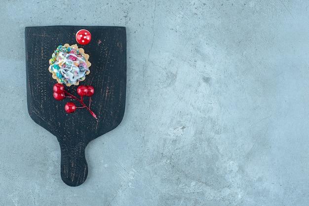 Cupcake met snoep bijvullen en kerst ornamenten op een zwart bord op marmeren oppervlak