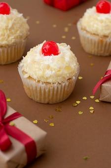 Cupcake met vanille botercrème, bruine achtergrond met geschenkdozen, verjaardagsconcept. zoet dessert.