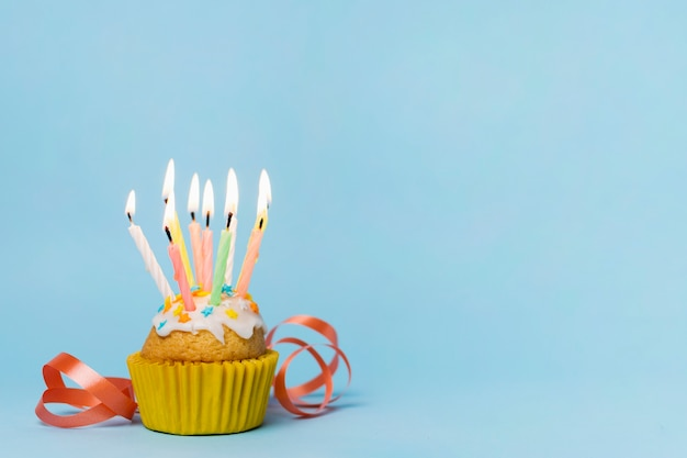 Cupcake met vele aangestoken kaarsen en exemplaarruimte