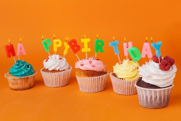 Cupcake met verjaardagskaarsen op oranje achtergrond