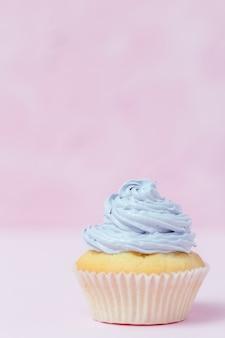 Cupcake met violette buttercream op pastelkleur roze achtergrond wordt verfraaid die.