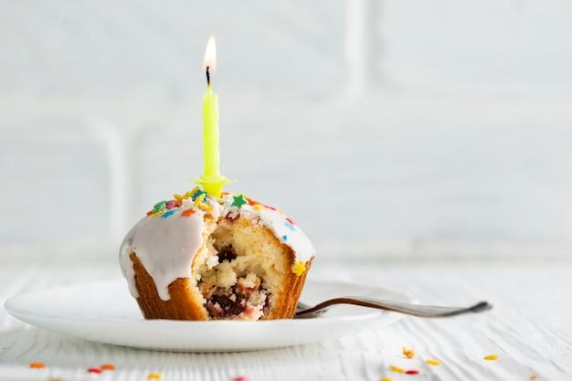 Cupcake met witte glans en kaars