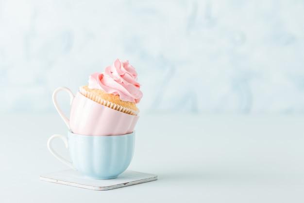 Cupcake met zachte roze roomdecoratie in twee koppen op blauwe pastelkleurachtergrond.