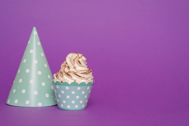 Cupcake naast papieren hoed