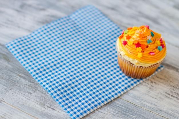 Cupcake op blauw servet glazuur van oranje kleur nieuw dessert in bistromenu lekker eten en goede service