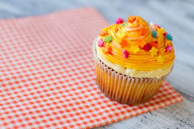 Cupcake op rood servet felgekleurde glazuur kies het beste dessert in café kleine suikerbloemen
