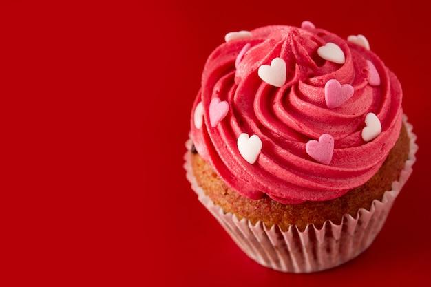 Cupcake versierd met suikerharten voor valentijnsdag op rode achtergrond