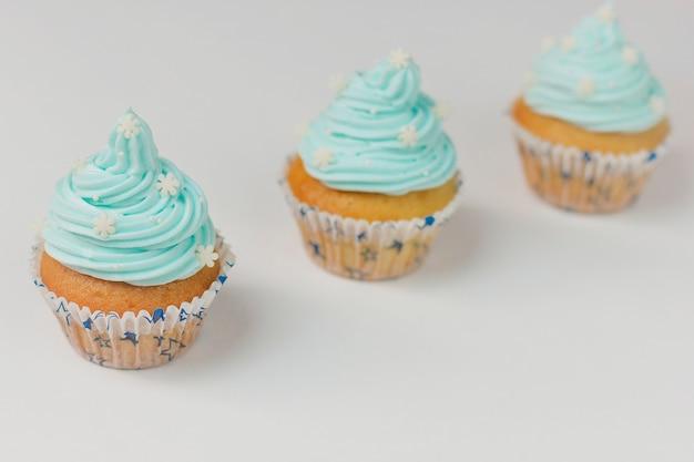 Cupcake versierd met suikersneeuwvlokken en blauwe room. kerstmis winter cupcakes