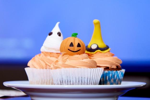 Cupcakepompoen voor halloween op blauw