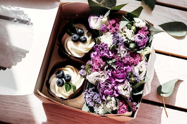 Cupcakes en bloemen in doos, feestelijke compositie voor valentijnsdag, verjaardag, 8 maart, bruiloft.