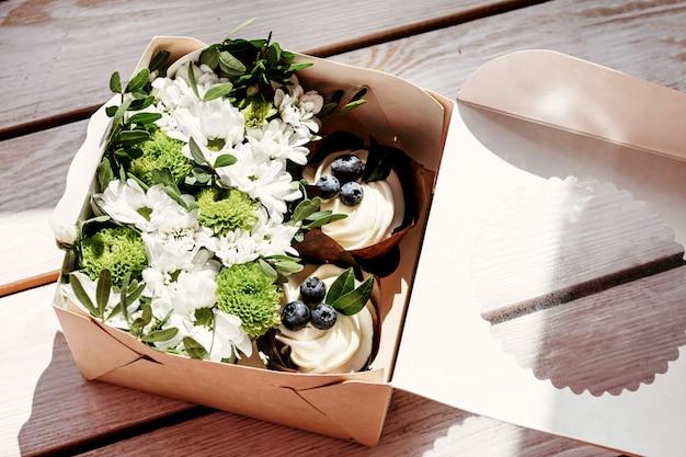 Cupcakes en bloemen in doos, feestelijke compositie voor valentijnsdag, verjaardag