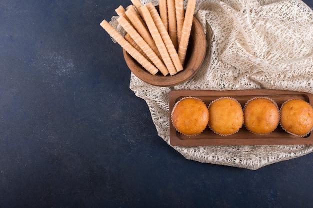 Cupcakes en wafelstokjes op een houten schaal in de bovenhoek