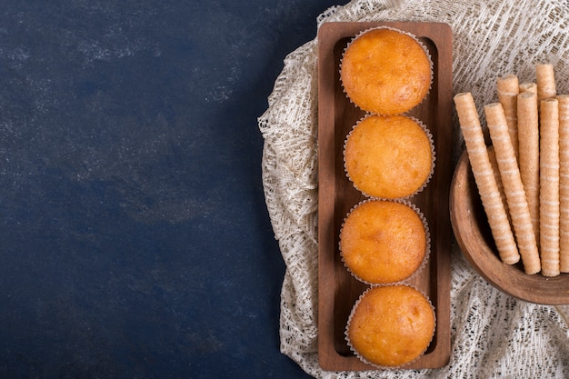 Cupcakes en wafelstokken op een houten schotel, bovenaanzicht