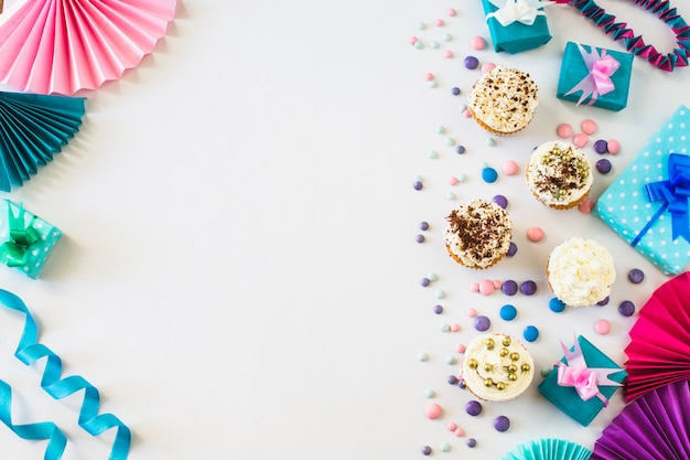 Cupcakes; handfan; snoepjes; geschenkdoos en lint op witte achtergrond