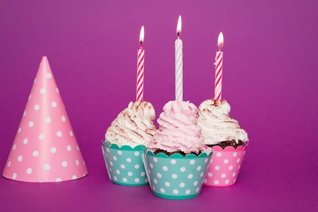 Cupcakes met aangestoken kaars naast hoed
