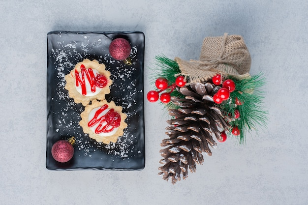 Cupcakes met aardbeiensaus op een zwarte schotel, gebundeld met kerstversieringen op marmeren oppervlak