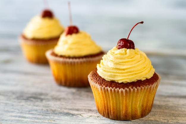Cupcakes met beige glazuur en kersen hoe je het leven zoeter kunt maken met de smaak van vanille