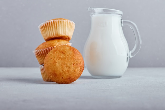Cupcakes met een potje melk op een grijze ondergrond.