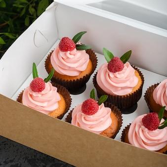 Cupcakes met frambozencrème, versierd met frambozen bovenop op geschenkverpakking.