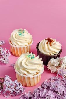 Cupcakes met lila bloemen op een roze tafel