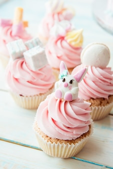 Cupcakes met roze crème versierd konijntje, marshmallow, macarons