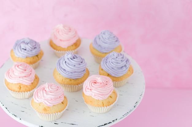 Cupcakes met roze en violette buttercream die zich op pastelkleur roze achtergrond bevinden.