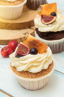 Cupcakes met vijgen, persimmon en roomkaas op een houten tafel