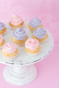 Cupcakes met violette en roze room op witte sjofele shic tribune op pastelkleur roze achtergrond.