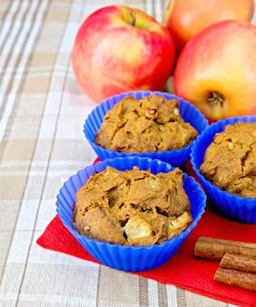 Cupcakes rogge met appel in siliconen mallen op rood papieren servet, appels en kaneel op een achtergrond van een linnen tafelkleed