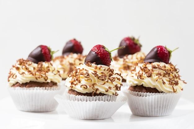 Cupcakes versierde met chocolade gedompelde aardbeien