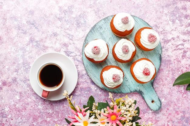 Cupcakes versierde slagroom en bevroren frambozen.