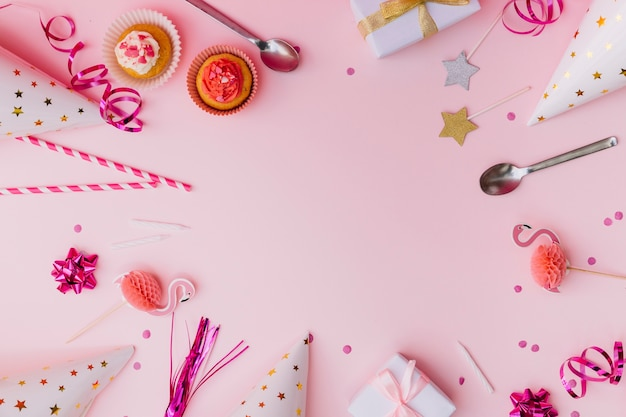 Cupcakes; wimpel; rietjes; prop; lepel; kaars; geschenkdozen; confetti en feestmuts op roze achtergrond