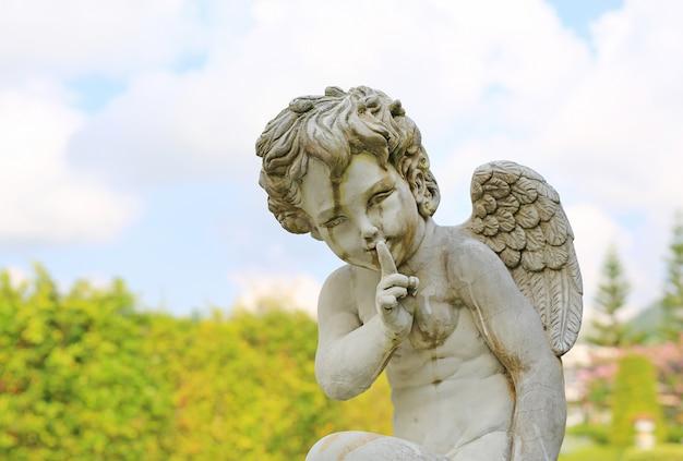Cupido-beeldhouwwerk in de zomertuin openlucht.