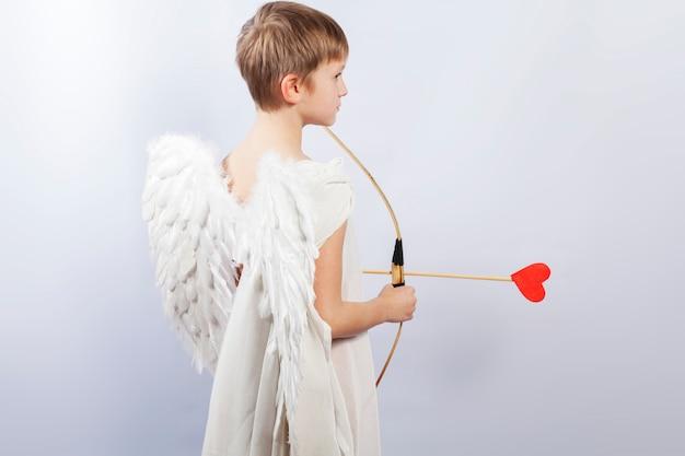 Cupido-jongen met vleugels en een schietende boog, aan het einde van de pijl een rood hart.