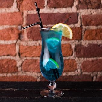 Curassao blauwe cocktail met citroen in een glazen bokaal