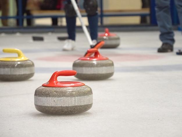 Curling steen op ijs van een indoor ijsbaan.