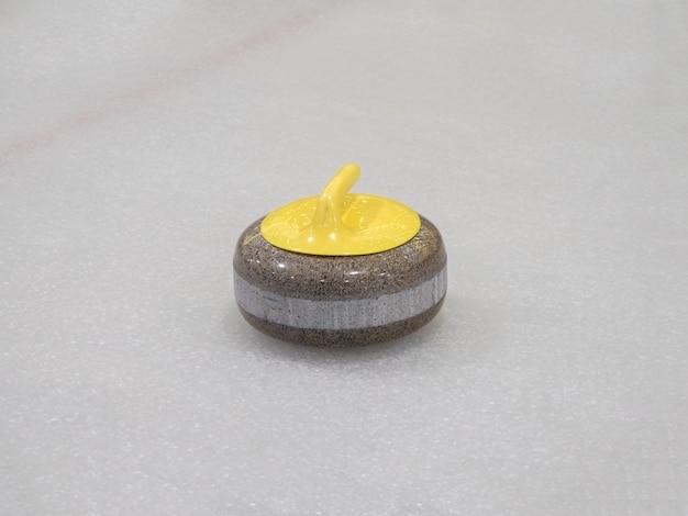 Curlingrotsen op een witte en blauwe ijsbaan.
