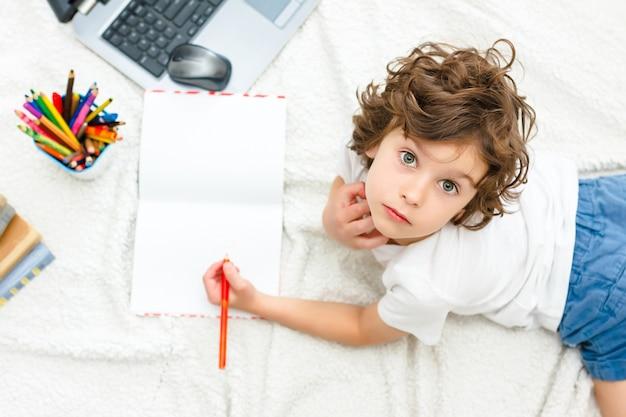 Curly boy is verloofd met computer schooljongen kijkt omhoog in de camera