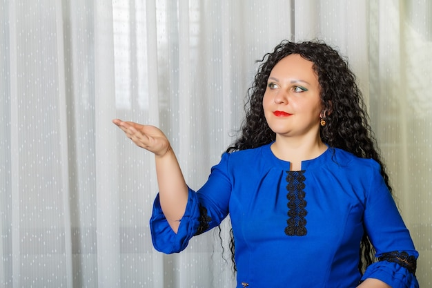 Curly brunette vrouw wijst naar iets met haar hand en praat erover. horizontale foto