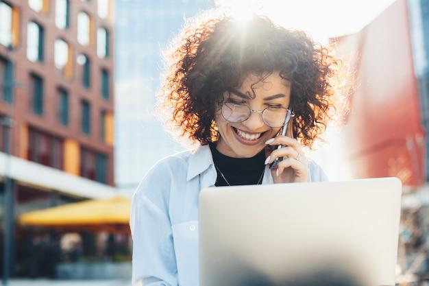 Curly haired bedrijfsmedewerker praat aan de telefoon tijdens het werken op een laptop en glimlach zittend op een bankje
