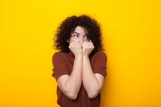 Curly haired blanke dame die haar gezicht bedekt met vuisten terwijl ze poseren op een gele muur