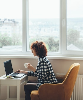 Curly haired blanke vrouw gekleed in vrijetijdskleding drinkt een kopje koffie met sandwich tijdens het werken op de laptop