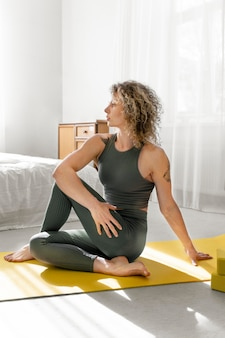 Curly-haired blonde vrouw doet yoga thuis