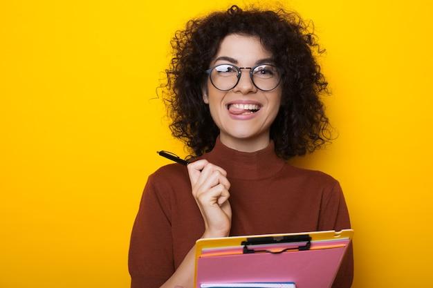 Curly haired brunette student kijkt door bril houdt een pen en een aantal boeken terwijl poseren op een gele achtergrond