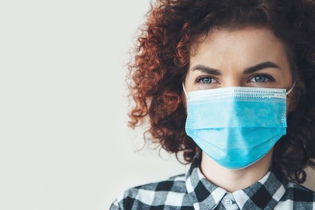 Curly haired brunette vrouw poseert dicht bij de camera op een grijze studiomuur met vrije ruimte in een masker