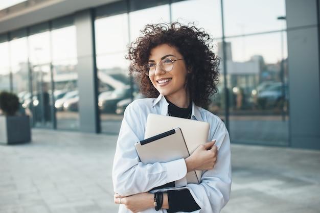 Curly haired business lady omhelst en houdt een laptop vast terwijl ze poseren met een bril voor een gebouw