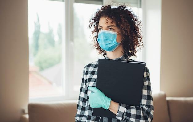 Curly haired dame met medisch masker op gezicht en handschoenen met sommige mappen is thuis poseren