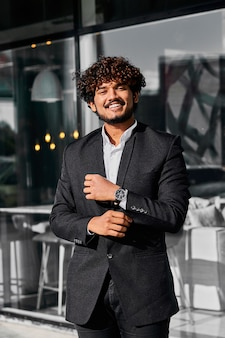 Curly-haired indiase zakenman staat buiten zijn kantoor.