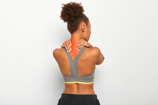 Curly haired jonge afro-vrouw masseert gespannen spieren, heeft pijn in nek en spasmen, donkere huid, draagt sportbeha, geïsoleerd op witte achtergrond